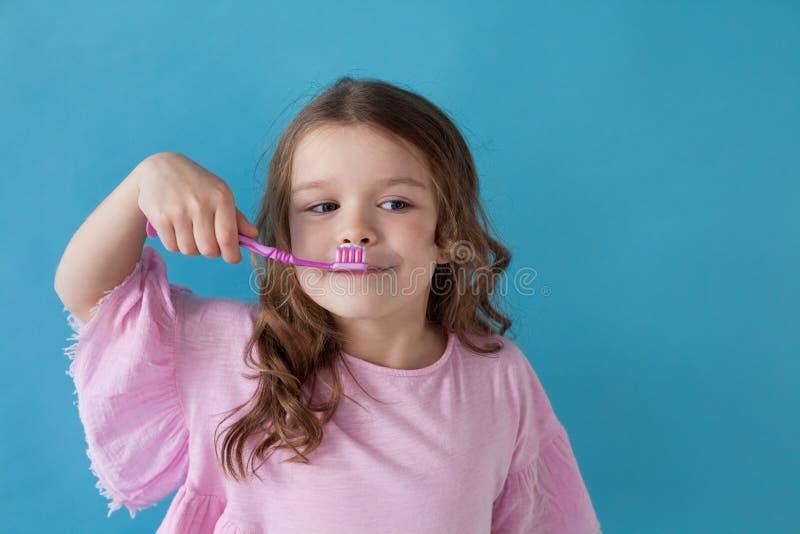 Het kleine mooie meisje maakt de Tandheelkunde van de tandentandenborstel schoon stock foto