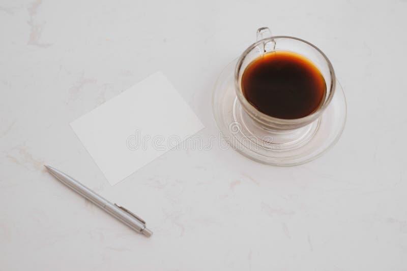 Het kleine notitieboekje met leeg gebied voor tekst of het bericht op bruine dekking en koffie vormt op lijst in ochtendtijd tot  royalty-vrije stock afbeelding