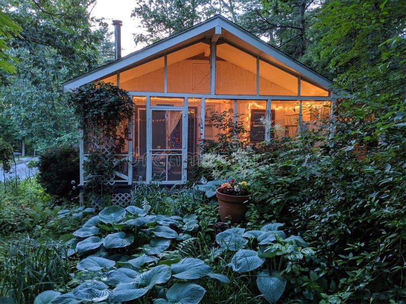 Het kleine Plattelandshuisje met Portiek fonkelt Lichten en omringd door tuinen stock fotografie