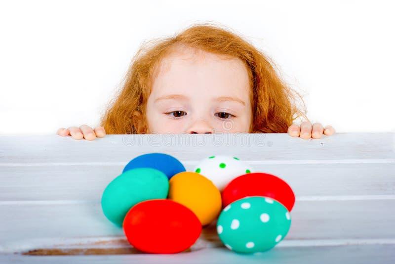 Het kleine roodharige meisje bekijkt paaseieren stock afbeeldingen