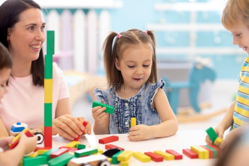 Het kleine speelgoed van de kinderenbouwsteen thuis of opvang Jonge geitjes die met kleurenblokken spelen Onderwijsspeelgoed voor royalty-vrije stock foto's
