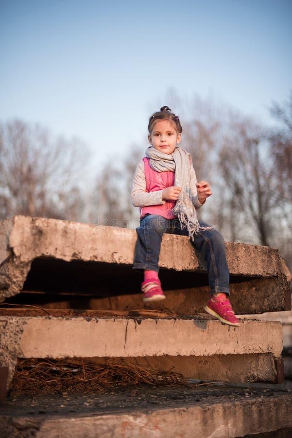 Het kleine vermakelijke meisje heeft uit op concrete platen stock foto's