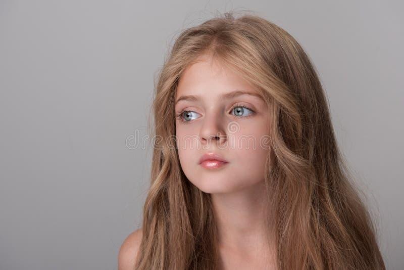Het kleine vrouwelijke kind stelt met pensiveness stock fotografie