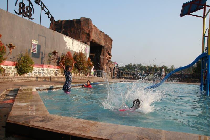 Het kleine water van het jonge geitjesspel cheerfully in pool stock afbeeldingen