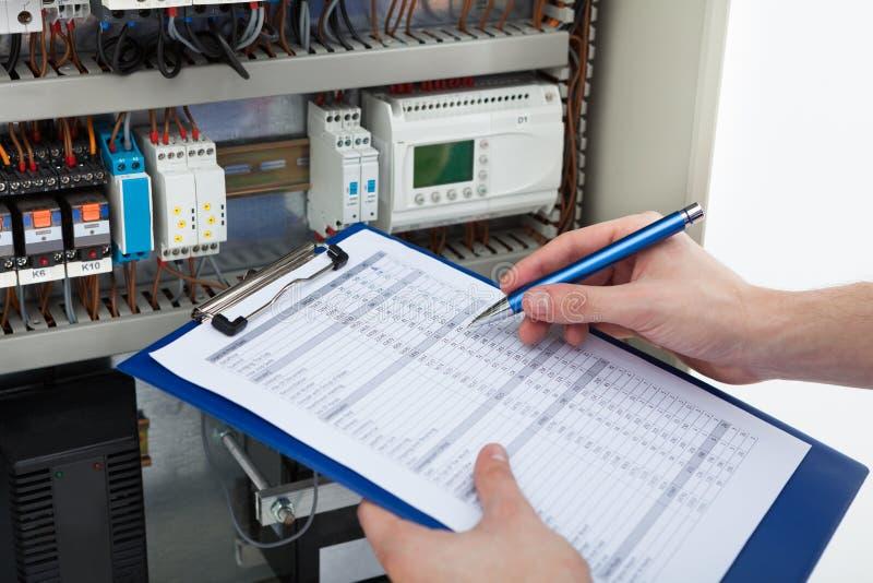 Het klembord van de elektricienholding terwijl het onderzoeken fusebox stock fotografie