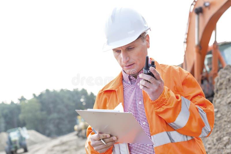 Het klembord van de supervisorlezing terwijl het gebruiken van walkie-talkie bij bouwwerf stock fotografie