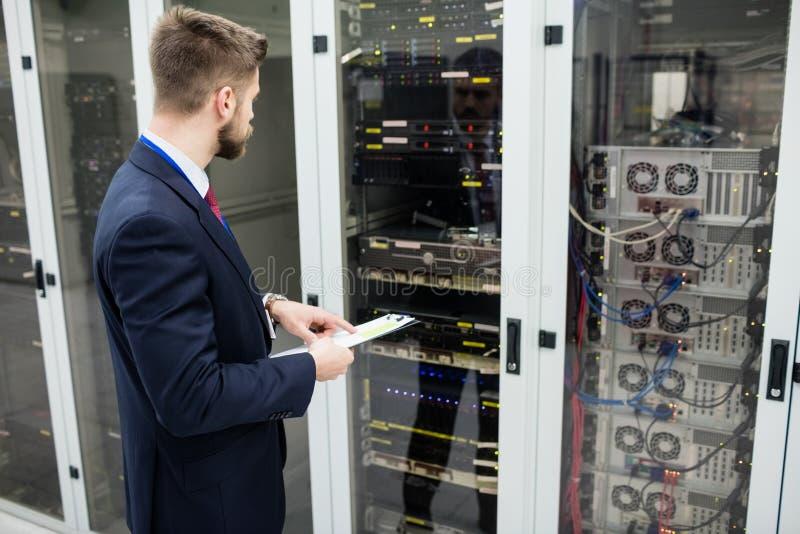 Het klembord van de technicusholding terwijl het analyseren van server royalty-vrije stock foto's