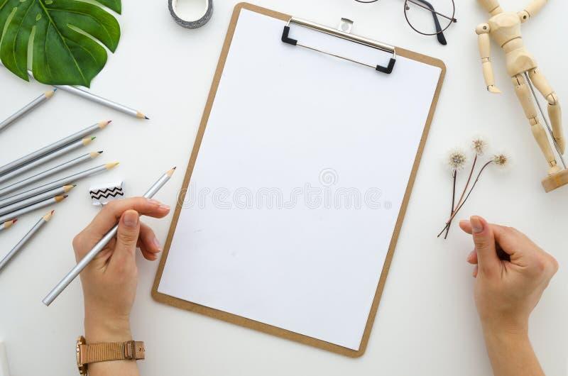Het klembordmodel, meisje trekt een potloodtekening, creatieve kunstenaarstekening a4, paardebloem, houten ledenpop die modelbove stock fotografie