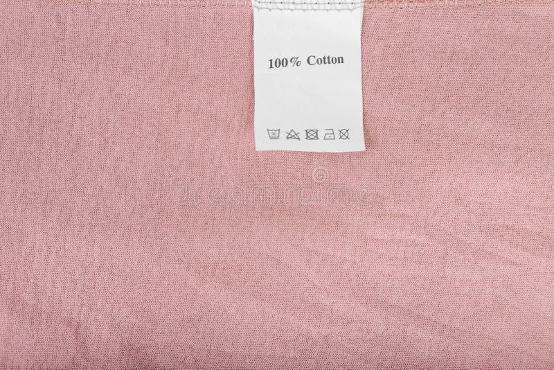 Het klerenetiket zegt 100%-katoen op roze textielachtergrond, omhoog sluit stock afbeeldingen