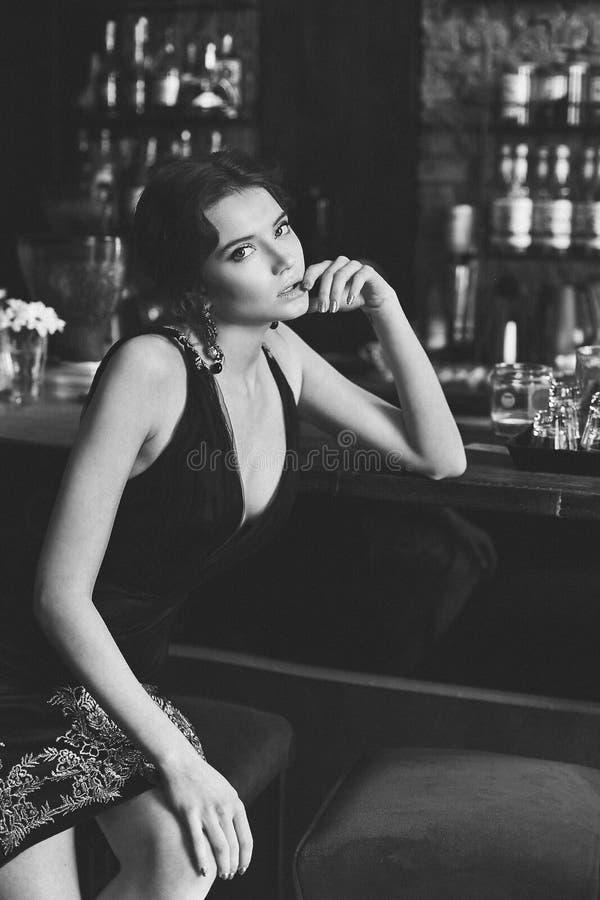 Het kleurloze foto - mooie en sexy donkerbruine modelmeisje in de zwarte modieuze kleding en in modieuze oorringen zit bij stock foto