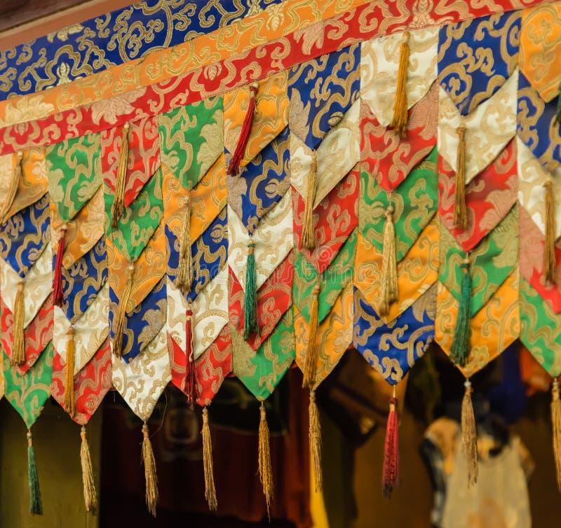 Het kleurrijke Boeddhismegordijn hangen op de deur stock foto