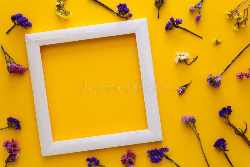 Het kleurrijke boeket van de droge herfst bloeit en wit houten kader die op gele document achtergrond liggen De ruimte van het ex royalty-vrije stock foto's