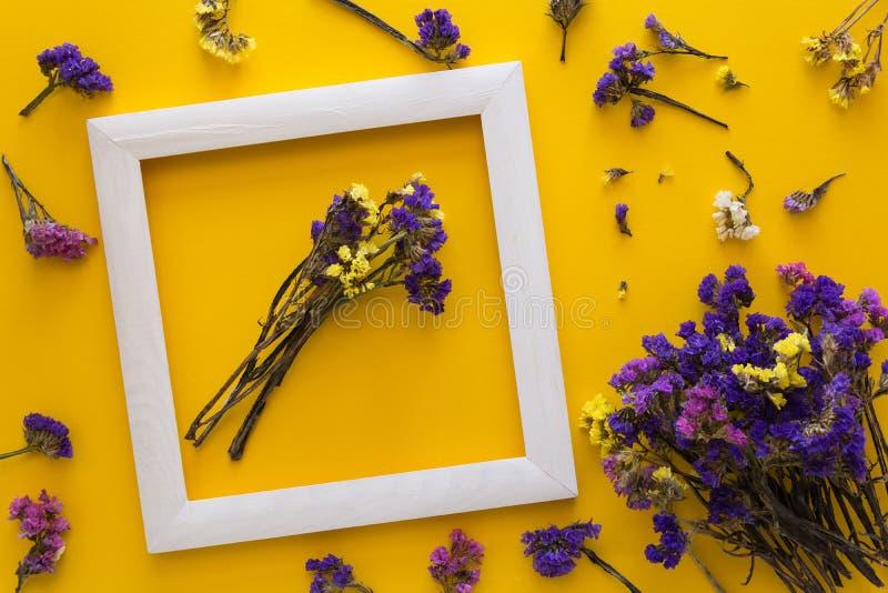 Het kleurrijke boeket van de droge herfst bloeit het liggen op een wit kader op gele document achtergrond De ruimte van het exemp royalty-vrije stock afbeelding