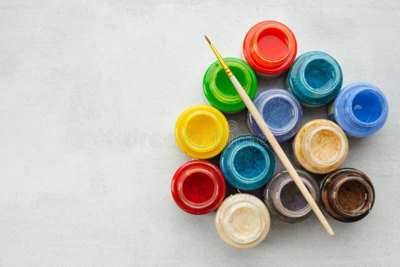 Het kleurrijke gebrandschilderde glas of de olie, acrylverven met verf borstelt op grijze achtergrond met exemplaarruimte stock foto's