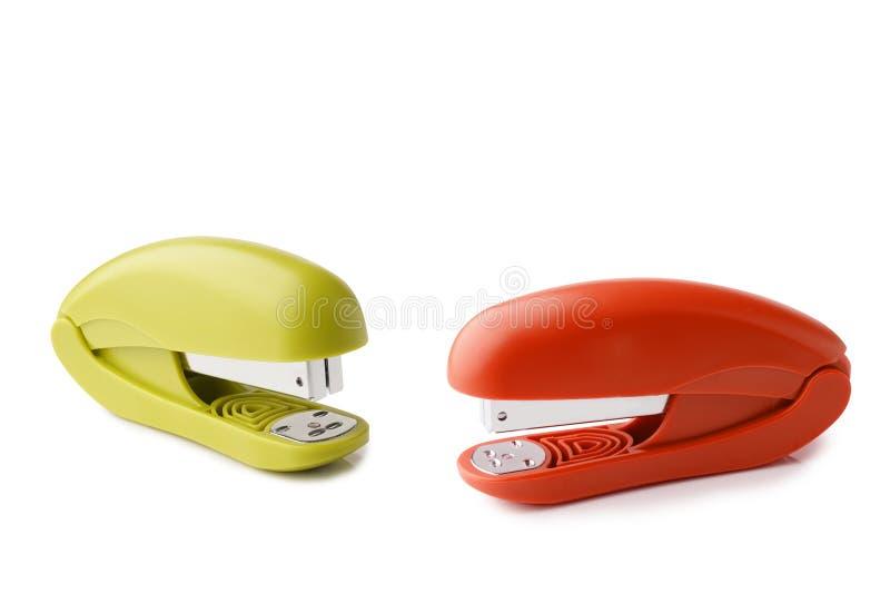 Het kleurrijke Handige Nietmachine Oranje en Groene Plastiek, Bureau levert Document Bindende die Nietmachine op een witte achter royalty-vrije stock afbeeldingen