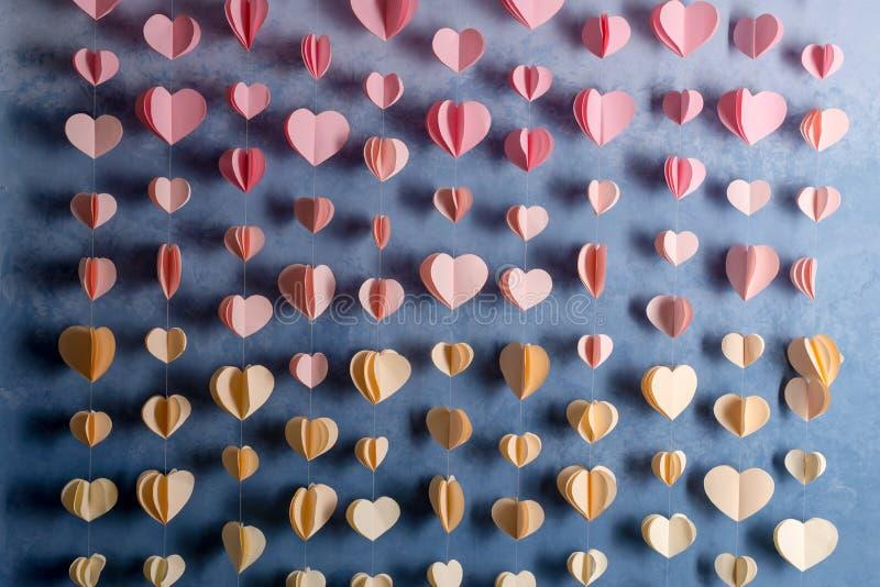 Het kleurrijke hartendocument slinger hangen op de muur De dagachtergrond van romantisch Valentine royalty-vrije stock foto's