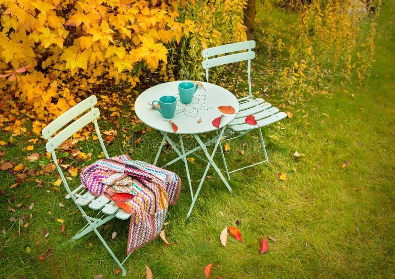 Het kleurrijke hoekje van de de herfsttuin met hete thee en deken stock foto