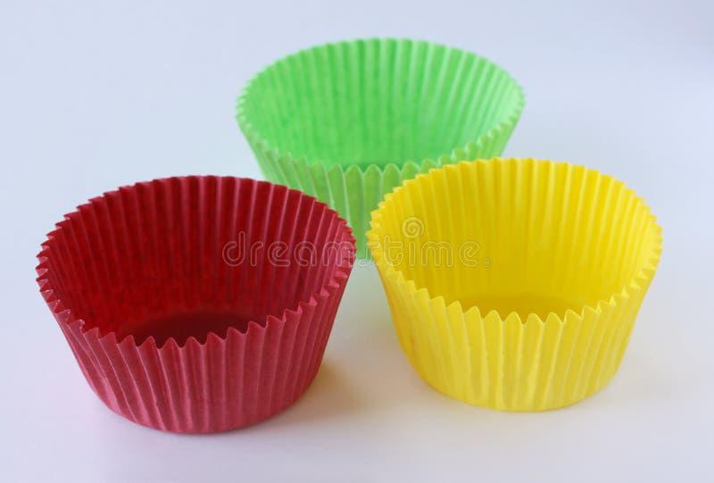 Het kleurrijke lege document vormt capsules voor muffins en cupcakes op witte achtergrond - bakseldessert - sluit omhoog op wit royalty-vrije stock foto's