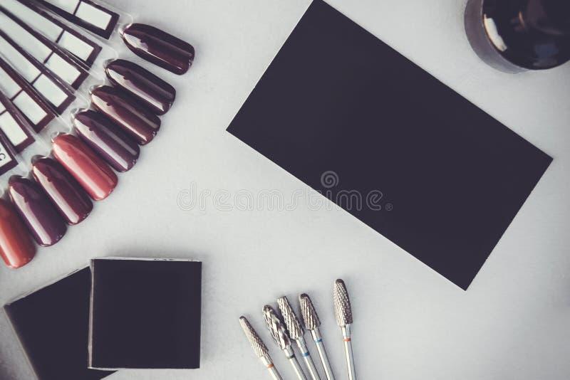 Het kleurrijke palet van het spijkerspoetsmiddel voor manicure op grijze achtergrond Inzameling van het poetsmiddelsteekproeven v stock fotografie