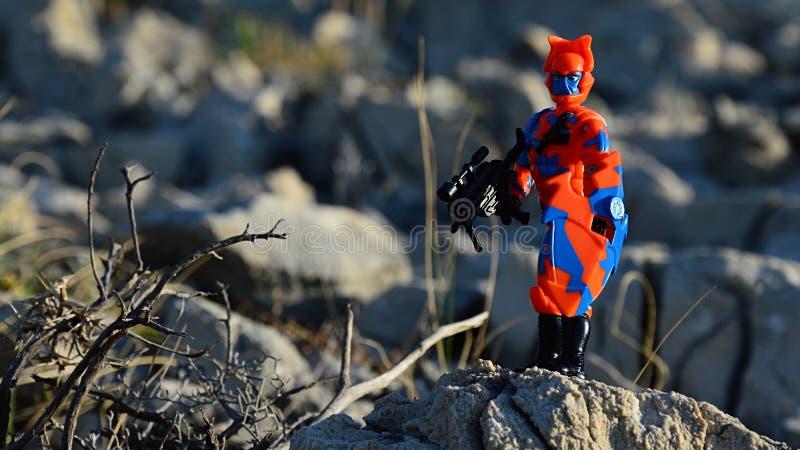 Het kleurrijke rode cijfer van de anb blauwe actie van Cobrateam noemde Steegadder zich bevindt op kustrots met futuristisch mach stock foto
