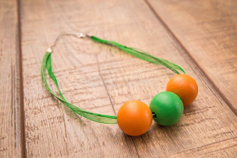 Het kleurrijke ronde die hout parelt halsbandhand met oranje en groene kleurenparels wordt geschilderd op een houten lijst stock fotografie