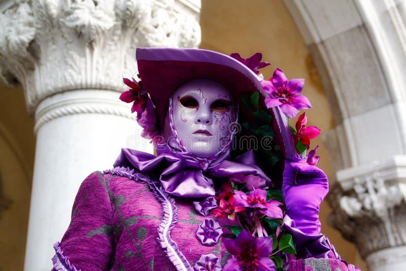Het kleurrijke roze-lilac masker en het kostuum van Carnaval bij het traditionele festival in Venetië, Italië stock afbeelding