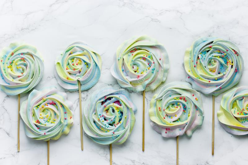 Het kleurrijke schuimgebakje met suiker bestrooit op een stok royalty-vrije stock afbeeldingen