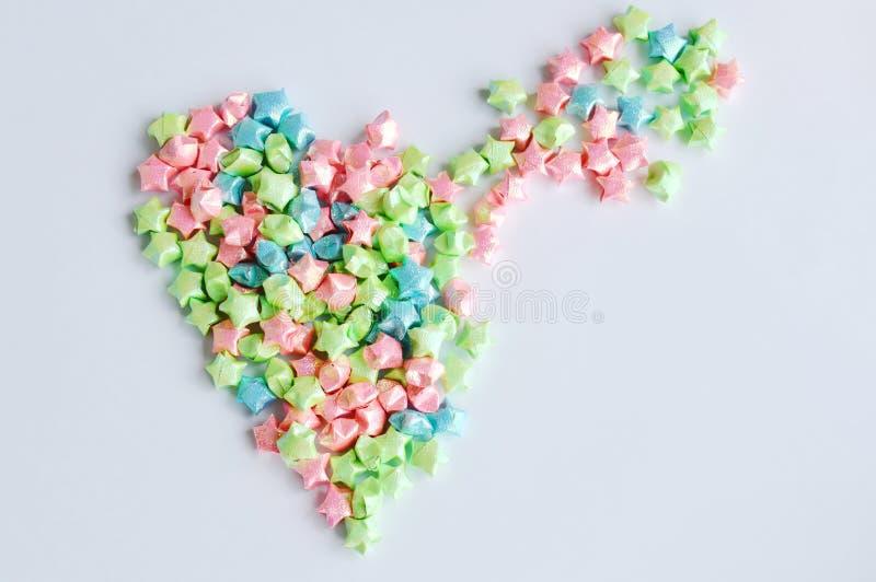 Het kleurrijke sterdocument uitspreiden aan hartvorm op witte achtergrond stock afbeelding