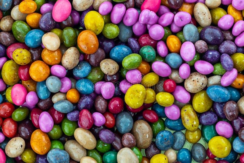Het kleurrijke suikergoed als achtergrond verglaasde violet geel grijs groen ongelijk de basisontwerp van het drageepatroon stock foto