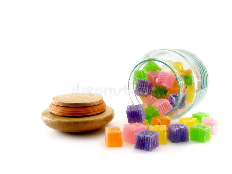 Het kleurrijke suikergoed die van de kubusgelei uit vacuümglasfles morsen met houten die deksel viel aan de grond op witte achter stock afbeeldingen