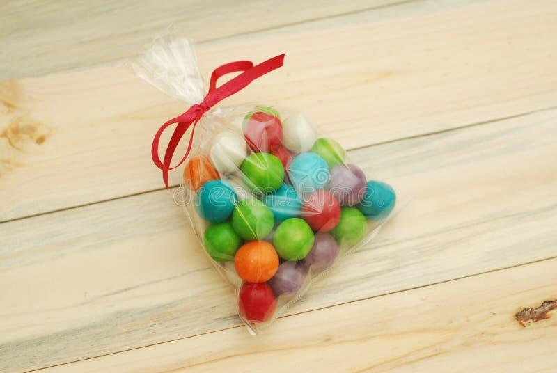 Het kleurrijke Suikergoed is Gevuld in Transparante Plastic Zak met Booglint over Houten achtergrond Giften voor Verjaardagsparti stock afbeelding