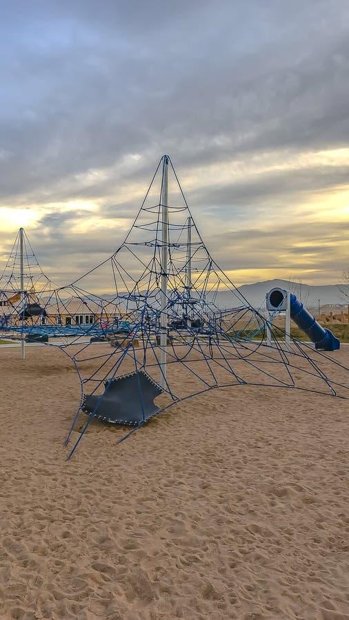 Het klimrek en de tunnels van de panoramakabel bij een speelplaats onder bewolkte hemel bij zonsondergang stock afbeelding