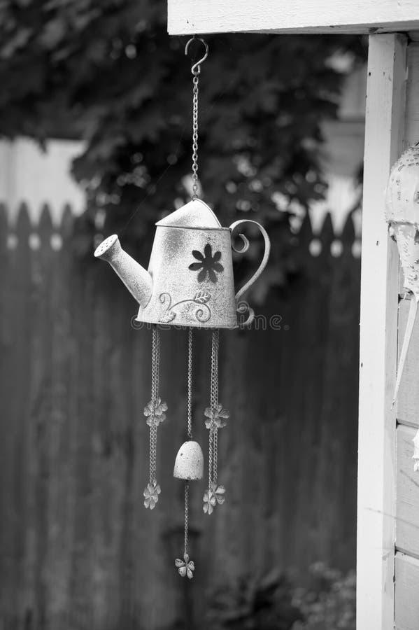 Het klokkengelui van de gieterwind het hangen van het dak van de tuinloods stock afbeeldingen