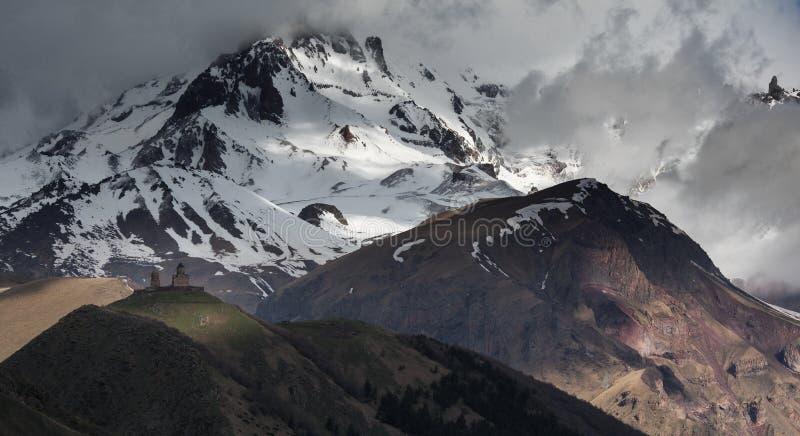 Het Klooster van de Gergetidrievuldigheid op een achtergrond van snow-capped Bergen van de Kaukasus en wolken, schot in Kazbegi stock foto