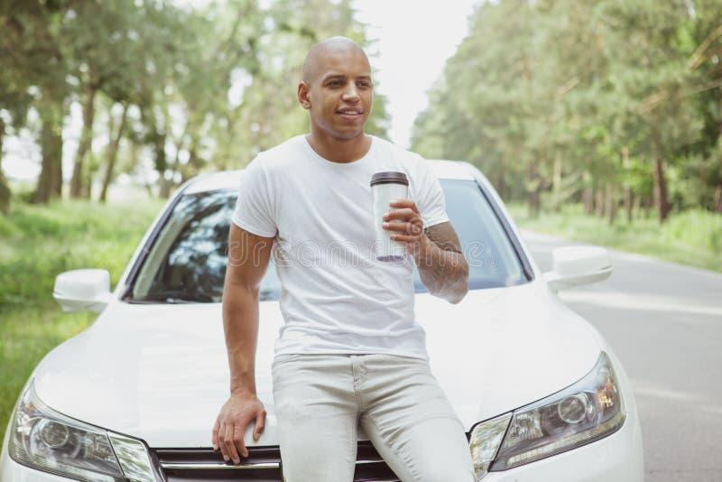 Het knappe Afrikaanse mens genieten die door auto op een roadtrip reizen royalty-vrije stock afbeelding