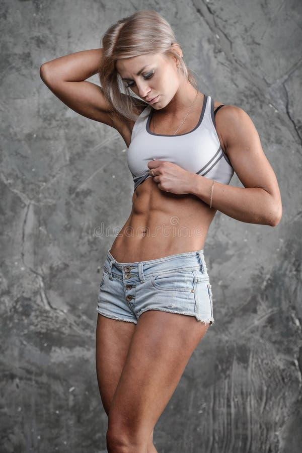 Het knappe atletische geschiktheidsmeisje stellen op een grijze achtergrond in st stock fotografie