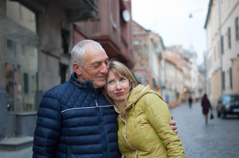 Het knappe bejaarde omhelst in openlucht zijn jonge blondevrouw het besteden tijd samen in de oude stad tijdens vroeg royalty-vrije stock foto's