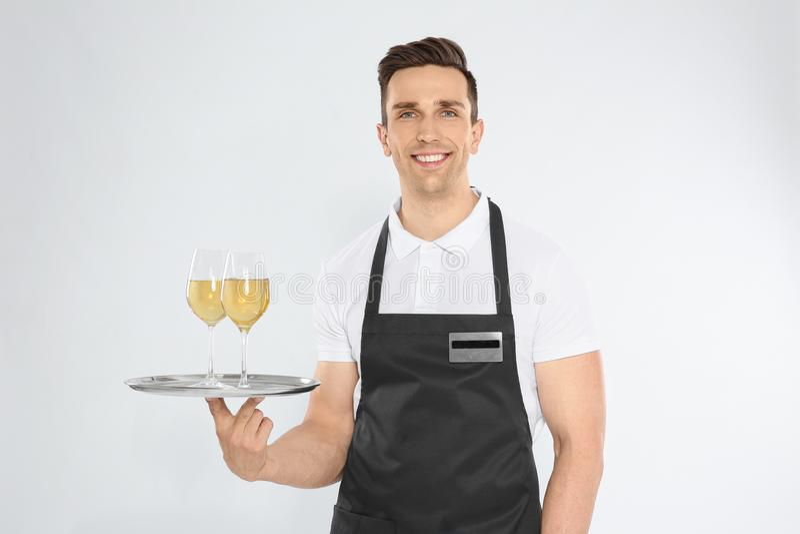 Het knappe dienblad van de kelnersholding met glazen wijn stock fotografie