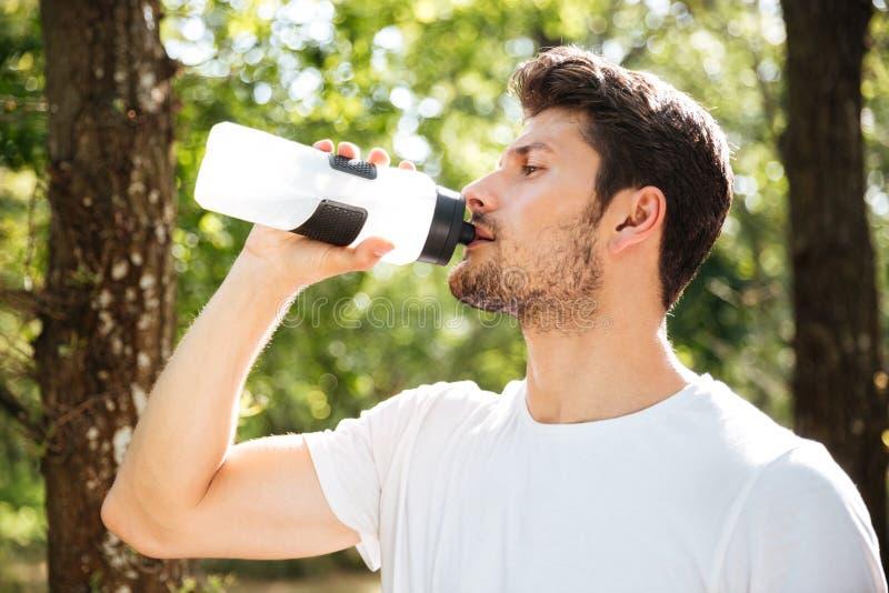 Het knappe drinkwater van de jonge mensenatleet in bos stock afbeeldingen