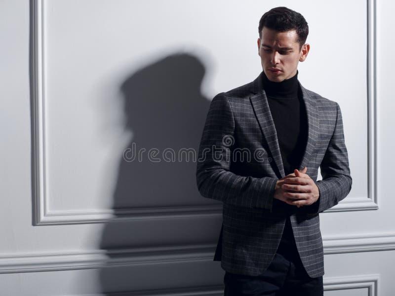 Het knappe, ernstige jonge mens stellen in studio dichtbij witte muur in elegant grijs kostuum, schaduw Bedrijfs mensenconcept stock foto