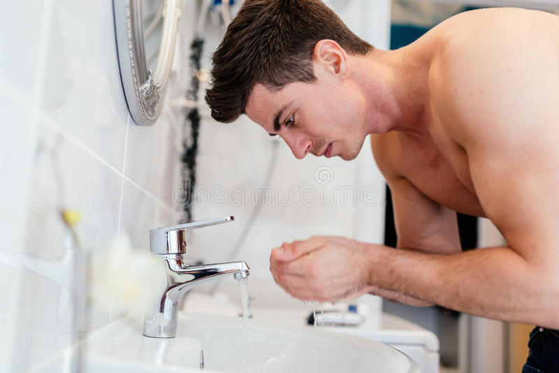 Het knappe gezicht van de mensenwas in badkamers stock foto's