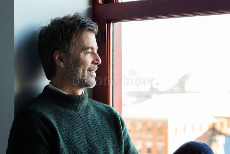 Het knappe het glimlachen mens ontspannen door het venster stock fotografie