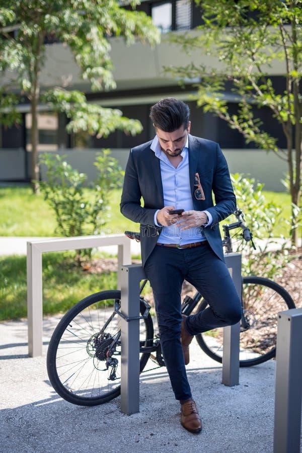 Het knappe jonge bedrijfsmens texting op zijn telefoon buiten stock afbeelding