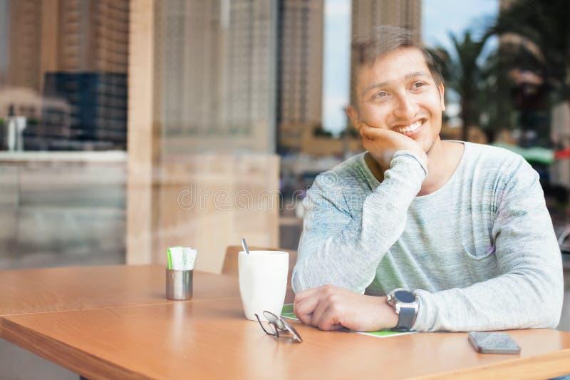 Het knappe jonge Indische mens ontspannen in een koffie royalty-vrije stock foto