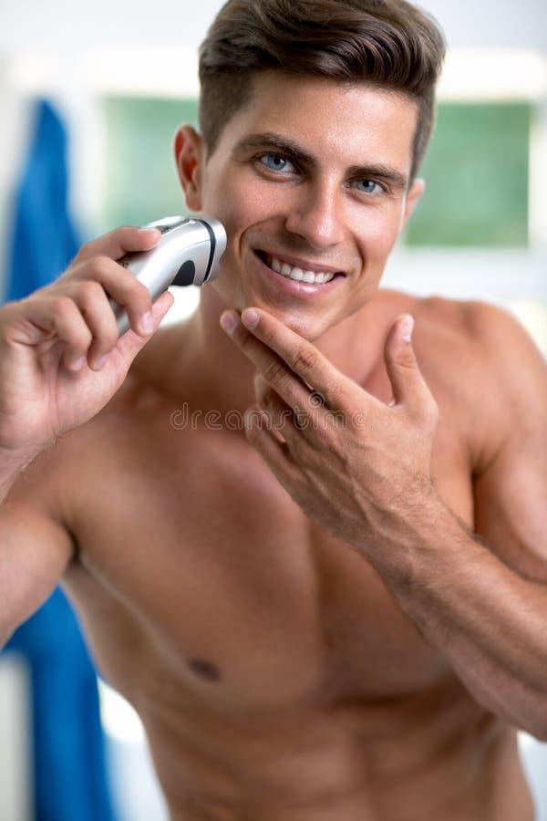 Het knappe jonge mens scheren met scheerapparaat stock foto's