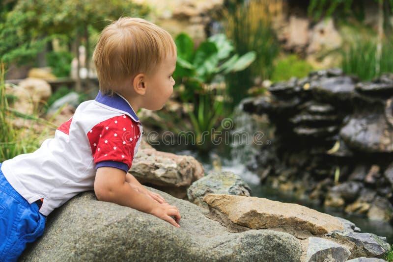 Het knappe kind van de 3 éénjarigenjongen op een gang in het park door de vijver op een zonnige dag royalty-vrije stock afbeeldingen