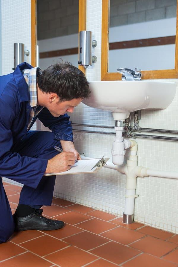 Het knappe loodgieter het inspecteren klembord van de gootsteenholding royalty-vrije stock foto's