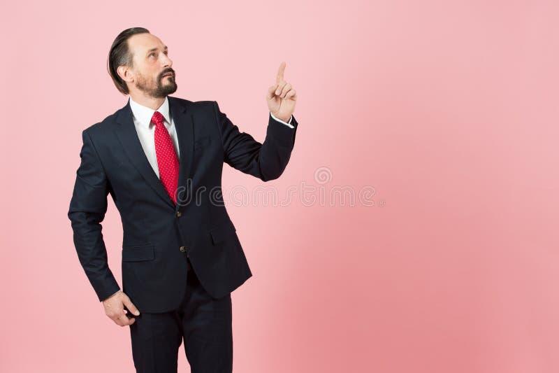 Het knappe mannetje die in zwart kostuum weg kant met vinger benadrukken en kijkt omhoog op roze achtergrond stock foto