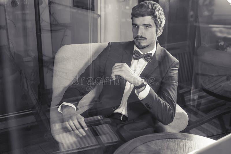 Het knappe mannetje heeft een Frans ontbijt bij koffie binnen stock foto