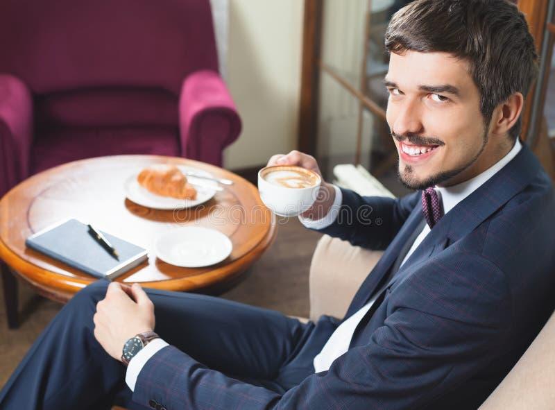 Het knappe mannetje heeft een Frans ontbijt bij koffierestaurant stock afbeelding